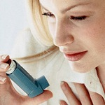 девушка снимает астматический приступ ингалятором