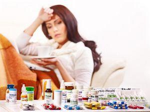больная девушка лечится чаем и медикаментами