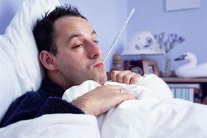 больной мужчина в постели с градусником