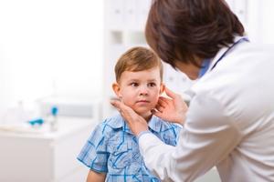 врач осматривает лимфотические узлы у мальчика