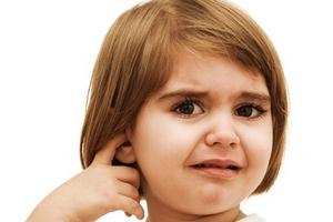 девочка указывает на болезненные ощущения в ухе