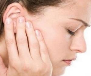 девушка указывает на больное ухо