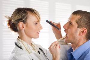 врач проводит диагностирование воспаления горла
