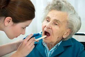 врач осматривает горло пожилой женщины