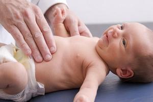 врач обследует новорождённого ребёнка