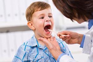 врач смотрит горло ребенку