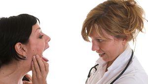 врач смотрит горло пациенту