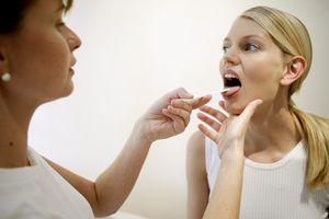 врач осматривает горло девушке